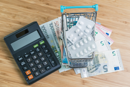 White package pills in miniature shopping cart on pile of Euro banknotes money with calculator on wood table, health care, medical or pharmacy cost concept, patient have to pay for their better life