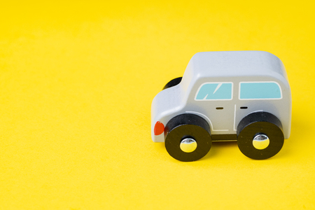 Cute wooden small toy car parking on vivid yellow background, car leasing, rental or insurance or automobile market concept.