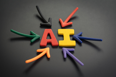 AI Artificial Intelligence concept, colorful arrows pointing to the alphabet combine acronym AI at the bright center on dark and black chalkboard, training computer to work for human.