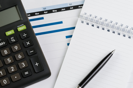 Finance or business quarterly performance review concept, calculator, pen with paper note on bar graph and chart report document on office desk.