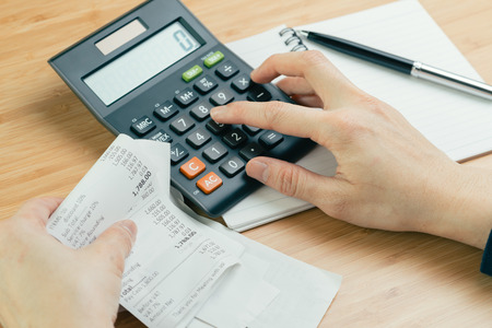 Cost and expense calculation or bill payment concept, hand put finger on calculator and black pen on paper notepad and holding pile of bills or receipt in the left hand on wooden table Stock Photo