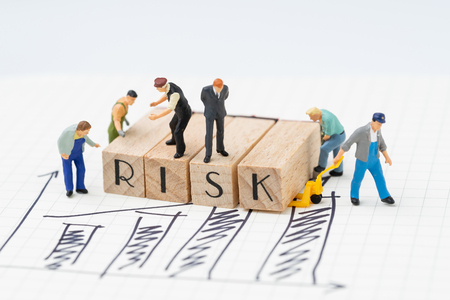 Risk assessment for business or investment, miniature figure businessman and company team standing on wooden stamp combine the word RISK and some worker try to move the stamp on revenue bar chart.