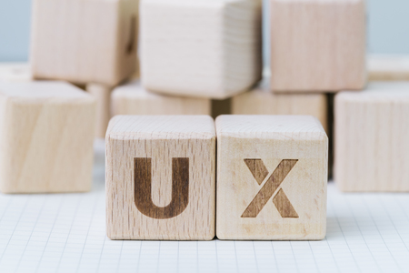 UX development, User Experience design concept, cube wooden block combining acronym UX on gridline notebook, user centric in modern world business, product and service design. Stock Photo