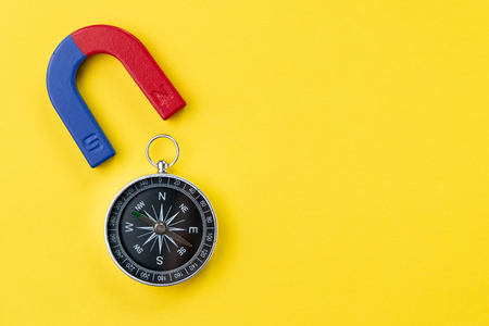 Horseshoe magnet with blue and red with compass on vivid yellow background with copy space using for special force or charm, attraction or magnetism to draw or lead to business goals. Stock Photo