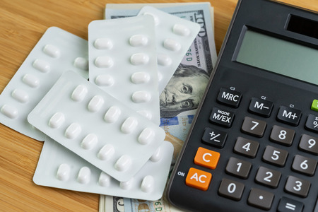 Pills in white package on pile of US Dollar banknotes money with calculator, health care, medical or pharmacy cost concept, patient have to pay for their better life