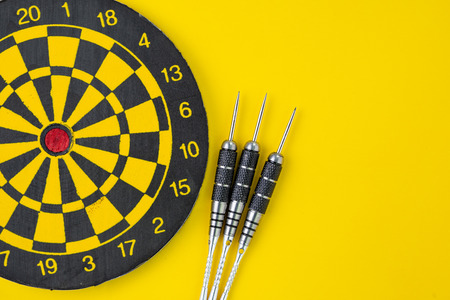 Flat lay of perfect black darts with dartboard on solid yellow background with copy space using as target and goals or three best important things you need to know concept.