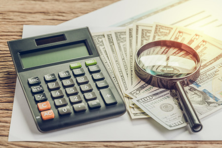 Tax, search for return or financial report review concept, magnifying glass on pile of US Dollar banknotes money with calculator on graph and chart profit and loss report on wood table. Stock Photo
