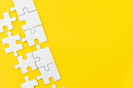 White jigsaw puzzle on vivid yellow background with copy space using for thinking strategy for business solution, teamwork, connection or idea for success.