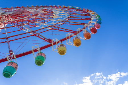 Amazing colorful ferris wheel in amusement park with sunshine blue sky in the morning with copy space, can be used as optimistic or start new day with happiness concept.