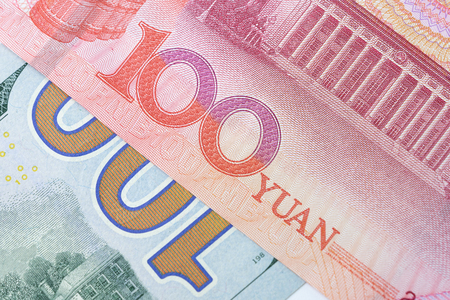 Closed up of 100 US Dollar banknote number on red 100 Chinese Yuan banknote, currency exchange or trade war between China and America concept.