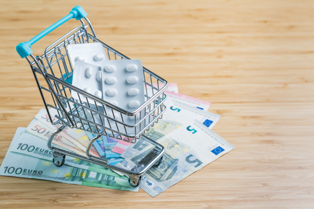 White package pills in miniature shopping cart or trolley on pile of Euro banknotes money on wood table with copy space, health care, medical or pharmacy cost concept