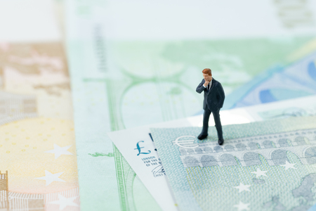 Brexit impact on Europe economy, financial, investment concept, miniature businessman leader figurine standing and looking at Euro and UK pounds sign on pile of banknotes.