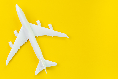 White toy commercial airplane on solid yellow background using as travel and transportation business wallpaper.