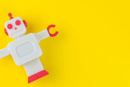 Chatbot or AI Artificial Intelligence or robotic concept, cute vintage look plastic robot on vivid yellow background. Stock Photo