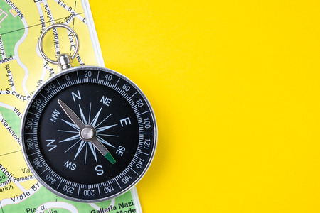 Compass on paper map with street for travel or driving navigation on vivid yellow background with copy space using for road trip on holiday or start new adventure or wanderlust life journey.