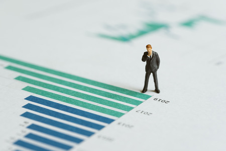 Miniature businessman leader standing with bar graph and chart of company annual report with vision of year 2019 revenue growth in green bar, forecast of company profit and stock investment concept. Stock Photo