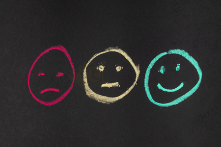 Chalk drawing face symbol angry or  displeased, natural and happy in red, yellow and green color on blackboard using as customer review, satisfaction score or user feedback on product and service.