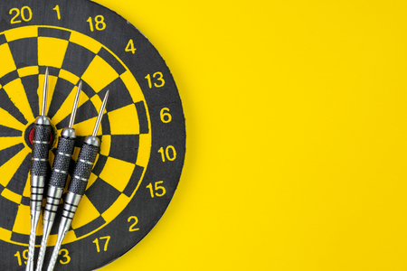 Flat lay of 3 black darts on dartboard on solid yellow background with copy space using as business target and goals or practice for success concept. Stock Photo