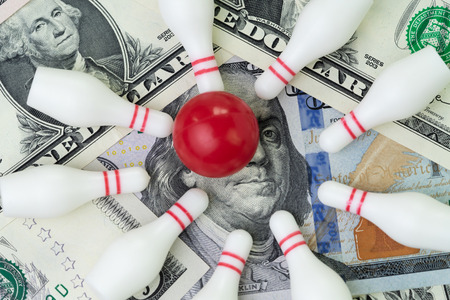 Red winning bowling strike ball surround with knocked down pins on pile of US dollar banknotes money, financial success target concept, goals on investment or profit in stock market concept. Stock Photo