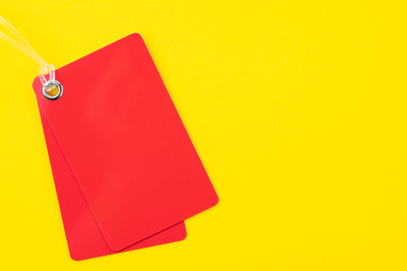 Red rectangle blank plastic red price tag label with transparent string on vivid yellow background with copy space, using for seasonal sale or promotion template. Stock Photo