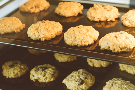 Closed up of hot baking oatmeal raisin cookies on black plate pan in the oven, using raisin and oat for main ingredient. Stock Photo