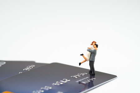 Miniature happy couple holding each other standing on pile of credit card on white background with copy space, success family financial management or online ecommerce shopping concept.
