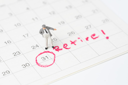 Happy miniature senior businessman standing on white clean calendar with the red circle on date with the word Retire using as planning for retirement with success investment and well prepare.
