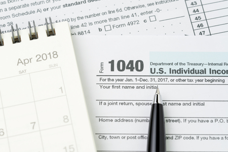 Pen on 1040 US individual income tax filling form with calendar, tax submission or revenue calculation concept.