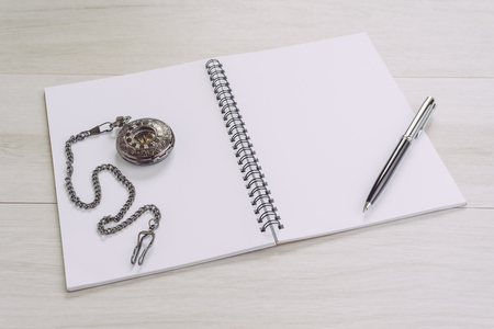 Blank empty white page note book opening with pen and vintage pocket watch on gray wooden table using as time, journal thinking, writing and creativity.
