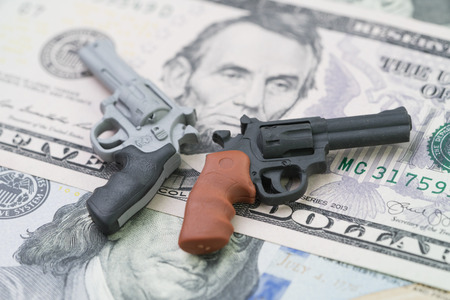 Big money in gun industry, gun control policy in united state of america concept, mass shooting protection, miniature toy guns on US dallar bill.