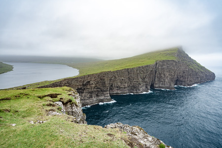 Amazing view of illusion lake on slave mountains of Tralanipan steep cliff in Vagar island, Faroe Islands, north Atlantic ocean, best destination for hiking, stunning sea stack with deep blue water.