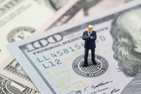 Miniature businessman leader standing and thinking on US Federal Reserve emblem on US dollars banknote as FED consider interest rate hike, economics and inflation control.