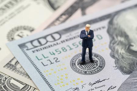 Miniaturgeschäftsführer, der über das Emblem der US-Notenbank auf der US-Dollar-Banknote steht und denkt, während die FED Zinserhöhung, Wirtschaft und Inflationskontrolle in Betracht zieht.