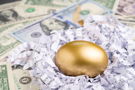 Cerrado de huevo de oro en papel triturado de informe financiero con pila de billetes de dólares estadounidenses utilizando como huevo de la suerte o acciones valiosas o fondos mutuos de éxito en inversiones a largo plazo.
