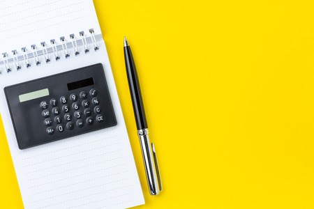 Financial activities, tax, budget or investment note, black calculator on blank small notepad and pen on vivid yellow background with copy space.