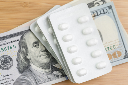 Pharmacy, health care or medical cost concept, white package of capsule pills on pile of US dollar banknotes money, patient have to pay for their better life.