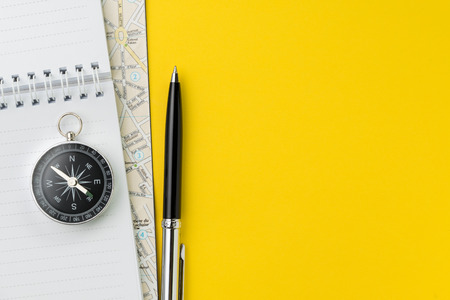 Flat lay or top view of black pen, notepad and map on vivid yellow background table with blank copy space, tourist, vacation or travel destination plan concept. Stock Photo