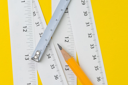 Yellow pencil and white measuring tapes with centimetre and inches on vivid yellow background, length, long or maker instrument and tools concept.