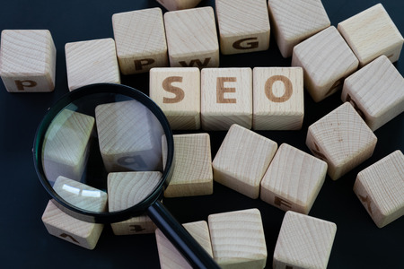 SEO, Search Engine Optimization top ranking in search result page concept, magnifying glass with wooden cube block with alphabet building the word SEO on blackboard background.