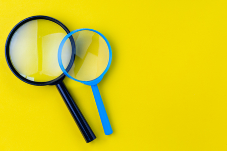 Black and bue magnifying glass, magnifier on yellow background with copy space using as search, transparent, science discovery or SEO concept. Stock fotó