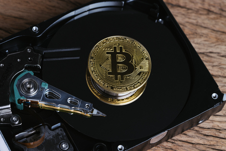 Bitcoin crypto currency digital money concept, shiny golden physical bitcoin coin with B sign on computer disk drive or hard drive data in low key on wooden table. Stock Photo