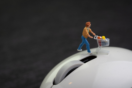 Miniature man with grocery in shopping cart or trolley walking on white computer mouse on dark black background with copy space using  online shopping or e-commerce website concept.