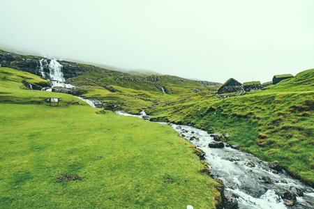 Beautiful peaceful rock house with green grass on the roof in Saksun valley next to the waterfall in foggy weather, Faroe Islands, North Europe, hidden gem for travel destination.