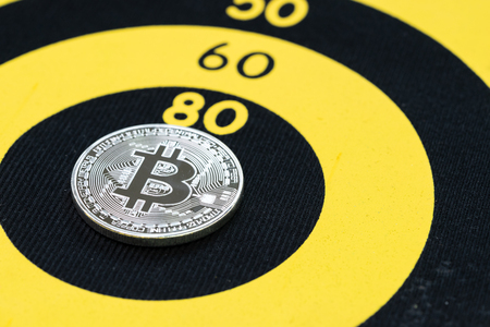 Bitcoin price target, physical bitcoin coin on center of yellow circle dartboard.