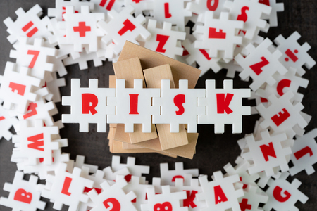 Risk management concept, white puzzle jigsaw with alphabet building the word Risk on top of wooden tower at the center of dark chalkboard.