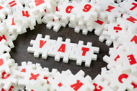 Value Added Tax, VAT concept, white puzzle jigsaw with alphabet building the word VAT at the center of dark chalkboard. Stock Photo