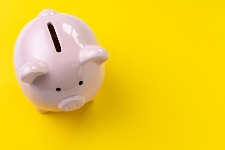 Top view of pink piggy bank on vivid yellow background with copy space, banking, budget, expense and saving concept. Stock Photo