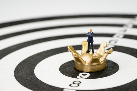 Business goal, target and achievement or leadership concept, miniature people confident businessman figurine standing on golden crown at the center of yellow and black dartboard with score number. Stock Photo