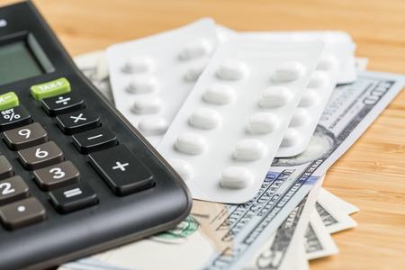 Pills in white package on pile of US Dollar banknotes money with calculator, health care, medical or pharmacy cost concept, patient have to pay for their better life. Stock Photo