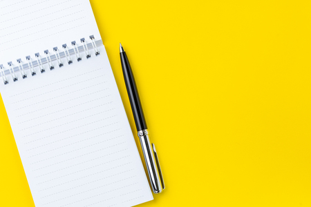 Top view of black pen with clean white notebook open with copy space on solid yellow table background for presentation, writer or school education, blogger, novel and friction or brand story concept.